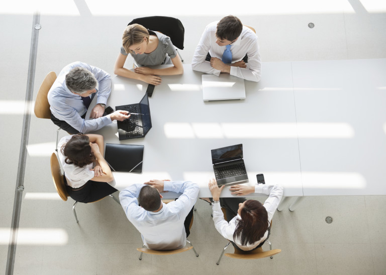 Overhead view of business people discussing in meeting with laptop on desk. Horizontal shot.
